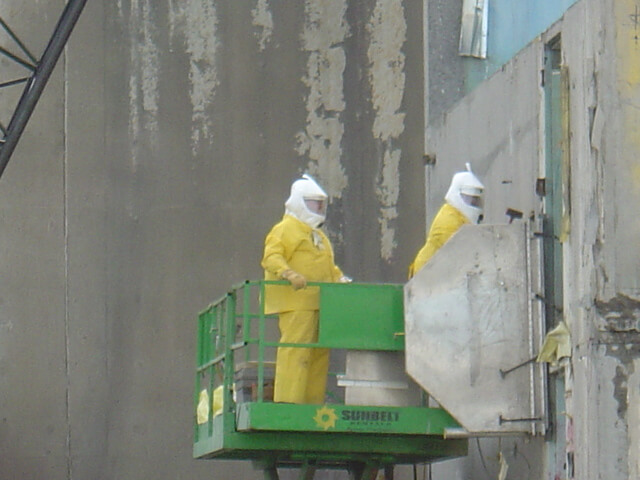 Shrouded circular saw cuts building into manageable slabs for hot cell demolition.